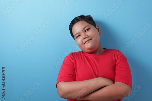 Fat Asian boy looks at the camera and smiles happily, crosses his arms in front Canvas Print