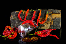 Hot Chilies Still-life, Red On Black Background With Dried Chilies And Chily Powder (close-up Detail Shot)
