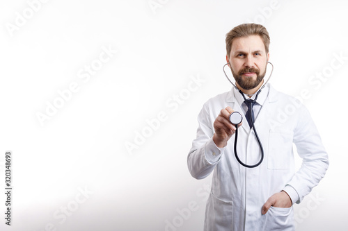 Photo Smiling bearded MD posing with stethoscope ready to auscultate isolated white ba