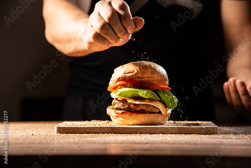 Fototapeta home made hamburger made by white sesame bun, tomato slice, salad, cheese, grilled meat and onion on wooden tray wooden table with cooking decorate chef hand in dark isolate background stock photo obraz