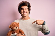 Young Handsome Man Holding Ted...