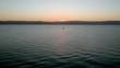Aerial drone view, slow movement: flying over the sea at sunrise or sunset, with a lone boat in the background, an orange horizon line and calm waves creating a relaxing pattern.