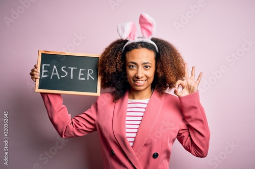 Photo African american woman with afro hair wearing bunny ears holding blackboard with