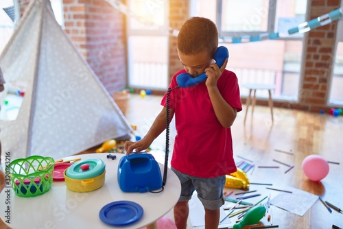 Obraz Adorable toddler playing with vintage phone around lots of toys at kindergarten - fototapety do salonu