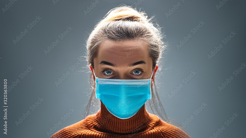 Fototapeta Woman wearing blue medical protective mask to health protection from influenza virus, epidemic and infectious diseases