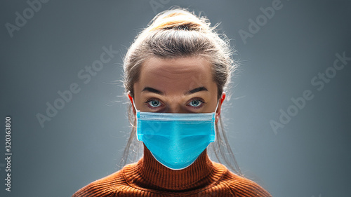 Obraz Woman wearing blue medical protective mask to health protection from influenza virus, epidemic and infectious diseases - fototapety do salonu