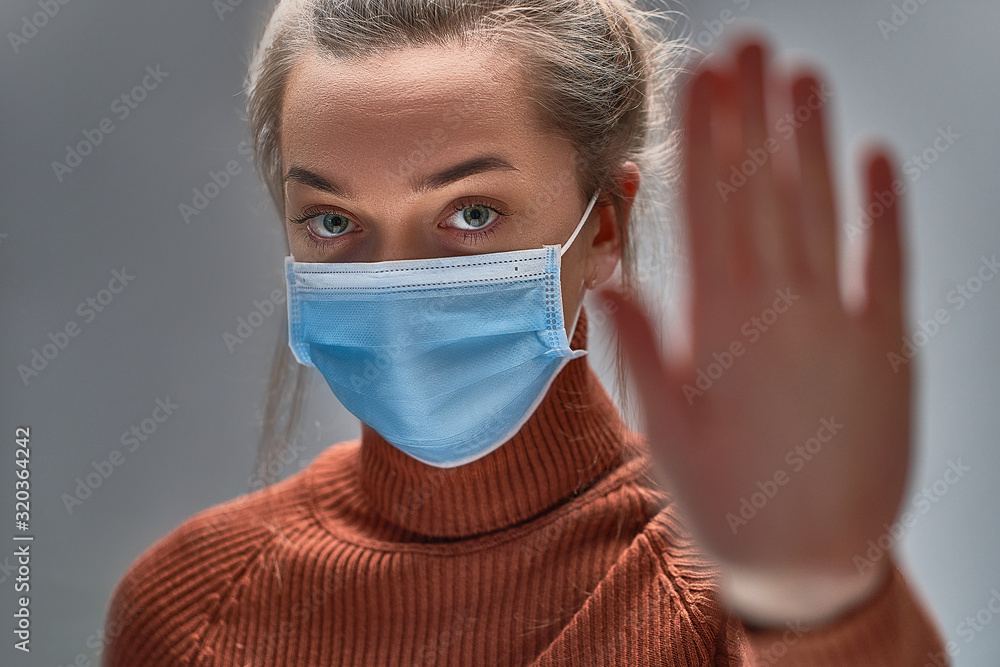 Fototapeta Stop the virus and epidemic diseases. Healthy woman in blue medical protective mask showing gesture stop. Health protection and prevention during flu and infectious outbreak