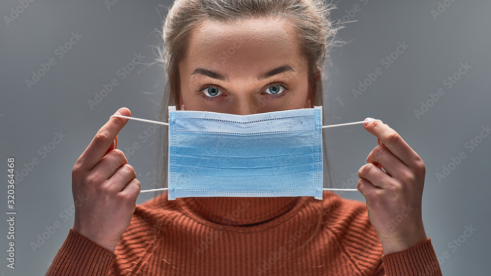 Fototapeta Healthy woman using medical protective mask to health protection and prevention from flu virus, epidemic and infectious diseases