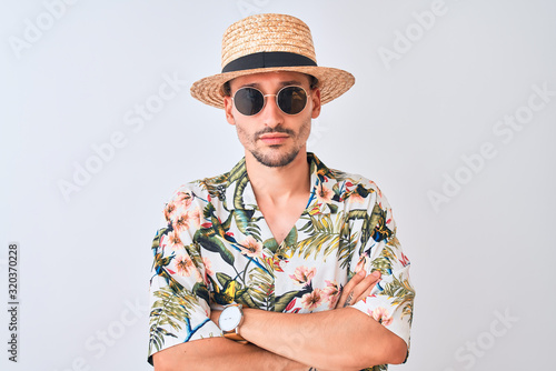 Young handsome man wearing Hawaiian shirt and summer hat over isolated background skeptic and nervous, disapproving expression on face with crossed arms. Negative person.