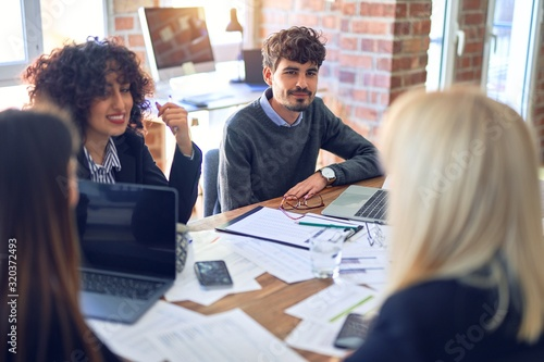 Fototapety, obrazy: Group of business workers smiling happy and confident. Working together with smile on face  using laptop and speaking at the office