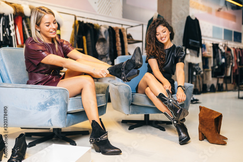 Fototapeta Beautiful young women trying leather boots in expensive boutique or store.. obraz