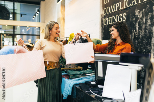 Fototapeta Beautiful young blond woman paying her new clothes buyed in expensive boutique with credit card. obraz
