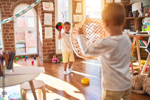 Obraz Adorable blonde twins playing basketball using wicker basket and ball around lots of toys at kindergarten - fototapety do salonu