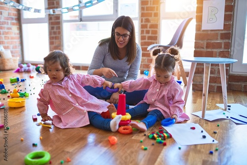 Obraz Young beautiful teacher and toddlers wearing uniform building pyramid using hoops at kindergarten - fototapety do salonu