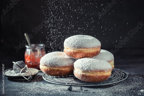 obraz PCV Delicious donuts with powdered sugar on dark table
