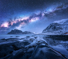 Milky Way Above Snow Covered Mountains And Rocky Beach In Winter At Night In Lofoten Islands, Norway. Cosmic Landscape With Starry Sky, Water, Stones, Snowy Rocks, Bright Milky Way. Beautiful Space