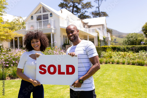 Happy young african american couple in the garden holding sold sign