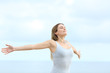 Happy woman breathing fresh air outstretching arms on the beach