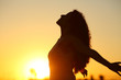 canvas print picture - Silhouette of a lady breathing fresh air at sunset