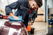 Young Man Cleaning An Automobile For A Customer