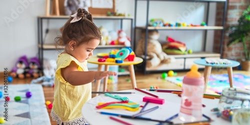 Obraz Beautiful toddler standing playing with toys on the table at kindergarten - fototapety do salonu