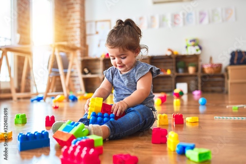 Obraz Beautiful toddler sitting on the floor playing with building blocks toys at kindergarten - fototapety do salonu