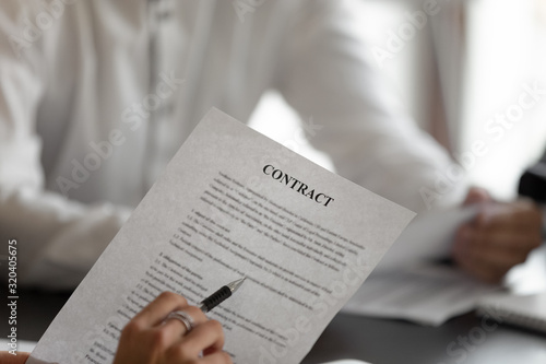 Fototapety, obrazy: Closeup man holding pen reading terms and conditions of contract