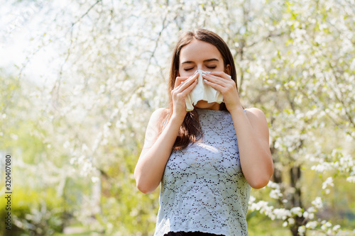 Sneezing young girl with handkerchief among blooming trees in spring park Wallpaper Mural