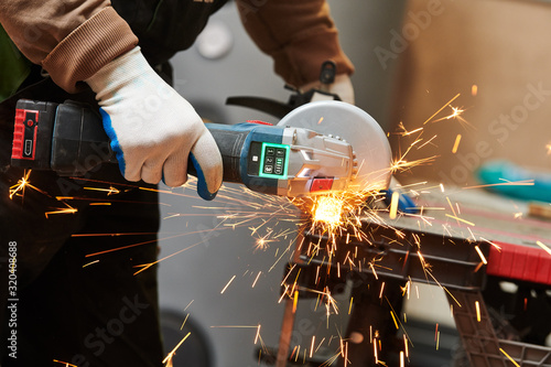 Fototapeta worker cutting metal tube with grinder machine and sparks