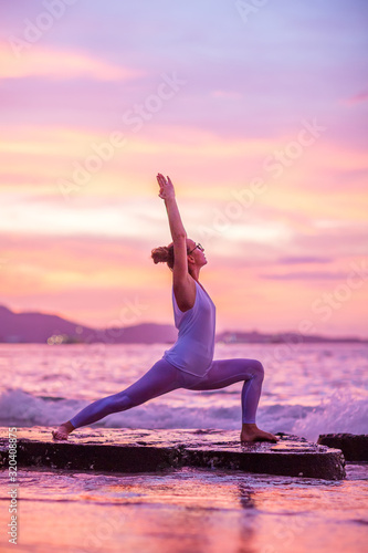Fotografie, Obraz Woman practices yoga at seashore