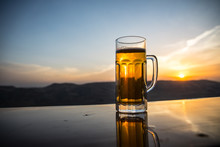 Glass Of Beer On A Beach At Sunset. Cooling Summer Drink Concept. Close Up Of A Glass Of Draught Beer With The Bokeh Of Sunlight Background