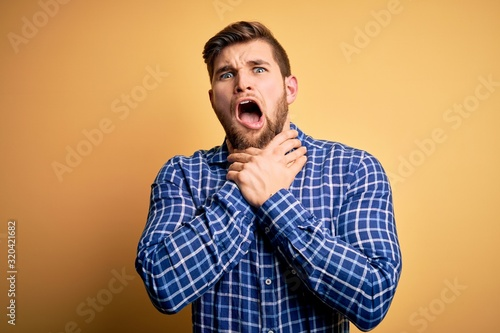 Photo Young blond businessman with beard and blue eyes wearing shirt over yellow background shouting suffocate because painful strangle