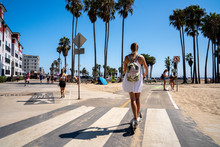 Beautiful Girl Riding An Electric Scooter Down The Venice Beach Bike Lane, Along The Beach And The Pacific Ocean With An Amazing View Of California In LA. Electric Scooter Style.