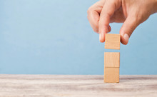 Business Man Puts Three Wooden Blocks On Top Of Each Other