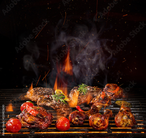Fototapeta Chicken legs, wings and steaks on the grill with fire flames obraz