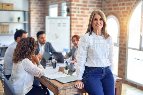 Obraz Group of business workers working together. Middle age beautiful businesswoman standing smiling happy looking at the camera at the office - fototapety do salonu