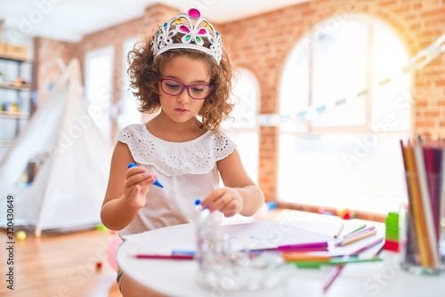 Obraz Beautiful toddler wearing glasses and princess crown sitting drawing using paper and marker pen at kindergarten - fototapety do salonu
