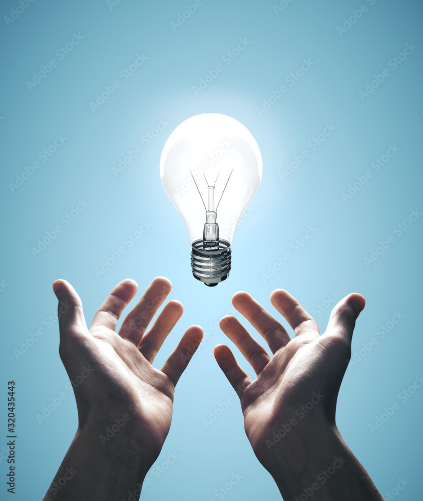 Fototapeta Hands holding bulb on blue background