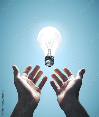 Obraz Hands holding bulb on blue background - fototapety do salonu