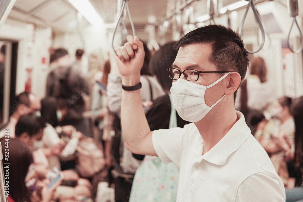 Fototapeta Middle aged Asian man wearing glasses and medical face mask on public train,  Wuhan coronavirus,  covid-19 virus outbreak, air pollution and health concept
