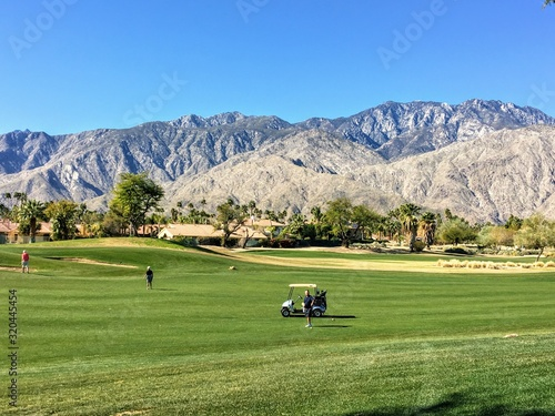 People out golfing at a beautiful golf course surrounded by mountains in the golf mecca of Palm Springs, California, United States.