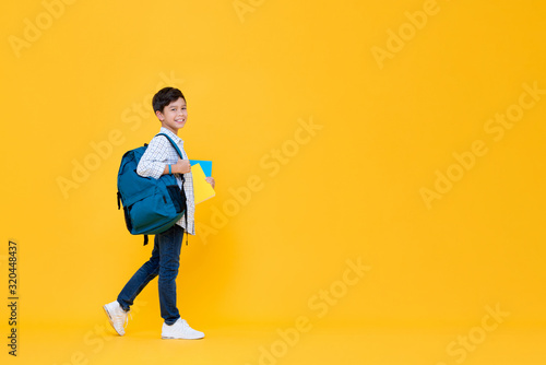 Fototapeta Handsome 10 year-old schoolboy holding books and backpack obraz