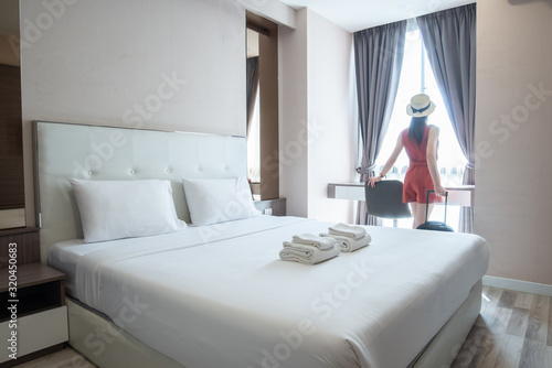 Photo Portrait of tourist woman standing nearly window, looking to beautiful view with her luggage in hotel bedroom after check-in