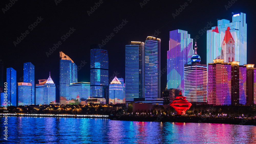 Scenic night view from the Urban park new town seaside of Qingdao, China.Seaside tourist town that is popular with Chinese people.Building lighting show With beautiful color lights at night.