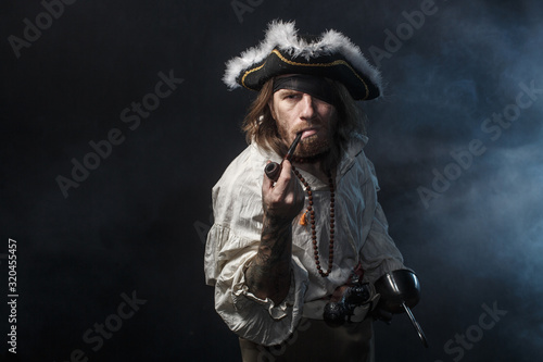 Fotografía medieval bearded pirate with a sword and gun