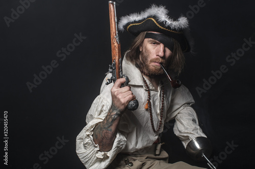Foto medieval bearded pirate with a sword and gun