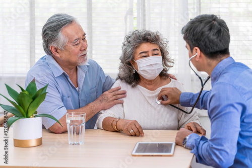 Doctor using stethoscope for auscultate Asian grandparent patient in house, serv Canvas Print