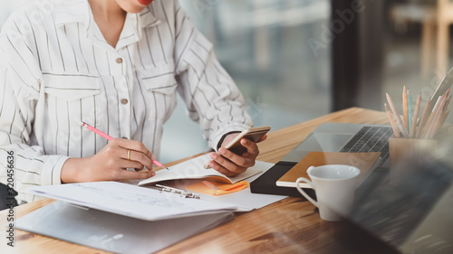 Cropped shot of young beautiful woman in striped shirt holding smartphone in hand and writing/taking note white sitting at the modern wooden desk with modern office as background Wallpaper Mural
