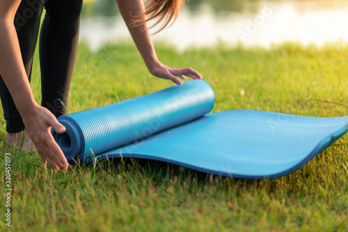 Obraz Young asian woman rolling blue yoga mat or fitness mat prepare to exercise in park, Healthy concept, Mind-body improvements concept. - fototapety do salonu