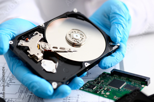 A male repairman wearing blue gloves is holding a hard drive from computer or laptop in hands Fototapete